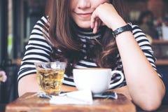 Een Aziatische vrouwenzitting in koffie met koppen van hete koffie en thee Stock Foto