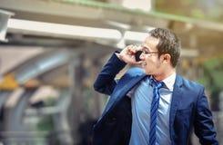 Een Aziatische zakenman spreekt aan zijn smartphone in een gedrang en een bus royalty-vrije stock afbeelding
