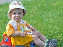 Een baby in de vrachtwagen op het gras Stock Afbeeldingen