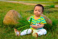 Een baby die op het gazon spelen (Chinees Azië, China,) Stock Foto
