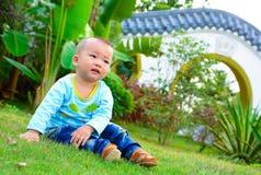 Een baby die op het gazon spelen (Chinees Azië, China,) Stock Afbeeldingen