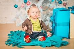 Een baby met giften bij Kerstboom Stock Foto