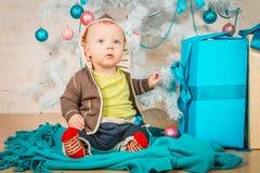 Een baby met giften bij Kerstboom Stock Fotografie