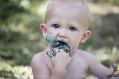 De ineenstortingsspruit van de cake: De jongen die van de baby cake op zijn sparren eten Stock Foto's