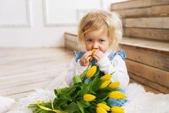 Een babymeisje in een blauwe kleding zit op de vloer met een groot boeket van gele tulpenbloemen en snuift uit de geur stock foto's