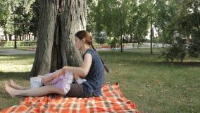 Een babymeisje in de overlapping van een jonge kindermeisjezitting op een deken spreidde over gras uit stock footage