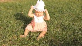 Een babymeisje die haar bonnet van haar hoofd, golvende handen en het kruipen uit het kader op alle fours proberen te trekken stock footage