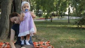 Een babymeisje die haar kleding verdraaien en proberen te lopen hield door een jong kindermeisje stock videobeelden