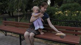 Een babymeisje die zich op alle fours bevinden en zich voor het Stokbrood uitrekken Het kindermeisje geeft haar een plak van het, stock footage