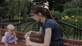 Een babymeisje die zich op alle fours op een bank bevinden Een kindermeisje glimlacht bij haar en zet een grote plak van Stokbroo stock videobeelden