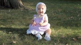 Een babymeisje in een bonnetzitting op het gras door zon wordt aangestoken te plaatsen die stock footage