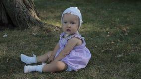 Een babymeisje in een bonnetzitting op het gras en de scheuren het stock videobeelden