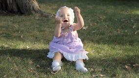Een babymeisje in een bonnetzitting op het gras en het slaan van haar handen stock videobeelden