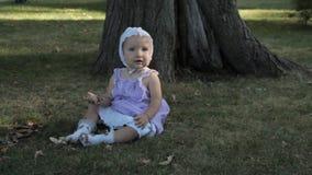 Een babymeisje in een bonnetzitting op het gras en holding een stok stock videobeelden