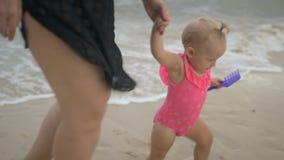 Een babymeisje in een roze zwempak op een strand met haar moeder stock video