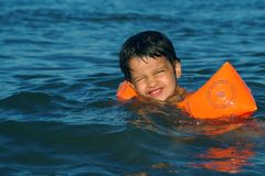 Een babymeisje zwemt bij het overzees royalty-vrije stock afbeeldingen