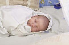 Een babyslaap in de voederbak Stock Fotografie