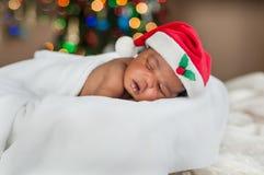Een babyslaap op z'n gemak in deken en Kerstmanhoed onder kleurrijke Kerstmislichten royalty-vrije stock afbeeldingen