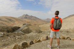 Een backpacker op een standpunt let op de rotsachtige bergen royalty-vrije stock fotografie