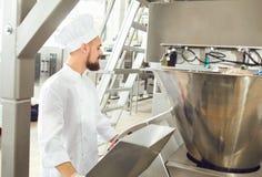 Een bakker controleert het proces om deeg voor bakselbrood te creëren royalty-vrije stock foto