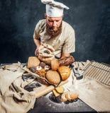 Een bakker die een eenvormig holdingsdienblad met vers voorbereide producten van zijn bakkerij dragen royalty-vrije stock foto