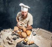 Een bakker die een eenvormig holdingsdienblad met vers voorbereide producten van zijn bakkerij dragen stock foto