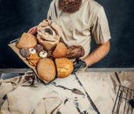 Een bakker die een eenvormig holdingsdienblad met vers voorbereide producten van zijn bakkerij dragen stock afbeelding