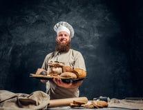 Een bakker die een eenvormig holdingsdienblad met vers voorbereide producten van zijn bakkerij dragen royalty-vrije stock afbeelding