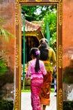 Een Balinees tiener klein schoolmeisje die traditionele lokale kleding dragen die een heilige tempel ingaan stock foto's