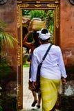 Een Balinese echtgenoot en een vrouw die traditionele lokale kleding dragen die een heilige tempel ingaan stock afbeelding
