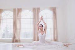 Een ballerina op een streng in witte kleren in een witte studio stock afbeeldingen