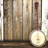 Een Banjo die op een houten omheining leunen. stock fotografie