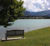 Een bank in de voorgrond en Meer Dunstan met bergen op de achtergrond in Cromwell, Nieuw Zeeland royalty-vrije stock fotografie