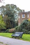 Een bank in het park langs de weg tegen de achtergrond van een klassiek Engels rood baksteengebouw royalty-vrije stock fotografie