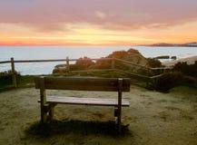 Een bank om op de Albufeira-zonsondergang te letten stock afbeeldingen