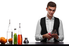 Een barkeeper die een capaciteit voor cocktails schoonmaken die, op een witte achtergrond wordt geïsoleerd Barman achter een bart stock afbeelding