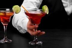 Een barman houdt een het glashoogtepunt van Margarita van cocktail op zijn hand, plakken van kalk op een donkere vage achtergrond Royalty-vrije Stock Fotografie