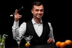 Een barman met houdt een lepel voor een schudbeker, een barteller met glazen, sinaasappelen en citroen op een zwarte achtergrond Royalty-vrije Stock Foto's
