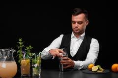 Een barman opent een schudbeker, glazen verschillende cocktails op een barteller op een zwarte achtergrond Stock Afbeelding