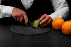 Een barman snijdt een groene kalk met een mes, een barteller met heldere sinaasappelen op een zwarte achtergrond Royalty-vrije Stock Foto