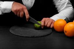 Een barman snijdt een groene kalk met een mes, een barteller met heldere sinaasappelen op een zwarte achtergrond Stock Afbeeldingen