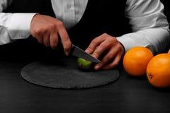 Een barman snijdt een groene kalk met een mes, een barteller met heldere sinaasappelen op een zwarte achtergrond Stock Foto's