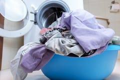Een bassinhoogtepunt van vuile wasserij op de badkamersvloer, vage wasmachine op achtergrond royalty-vrije stock foto's