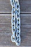 Een Bebouwd Close-upbeeld van een Verbonden Ketting Metaalketting over Houten Achtergrond royalty-vrije stock fotografie