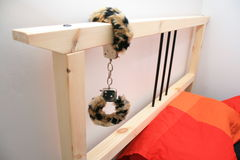 Een bed met handcuffs in bijlage Royalty-vrije Stock Foto