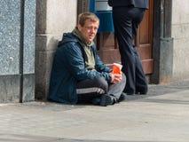 Een bedelaar zit onder een contant geldpunt in de Straat van O ` Connell in Dublin Ireland die een Euro of twee zoeken om hem doo royalty-vrije stock fotografie