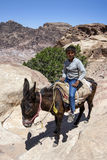 Een Bedouin jongen berijdt zijn ezel dichtbij de Hoge Plaats van Offer bij Petra in Jordanië Royalty-vrije Stock Afbeelding