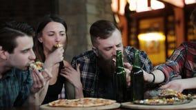Een bedrijf van gelukkige vrienden bij een koffielijst eet pizza, drinkt bier en heeft pret stock footage