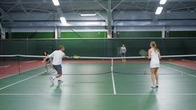 Een bedrijf van het tennis van het vriendenspel op de sportengrond, de volwassen mannen en de vrouwen werpen een tennisbal aan ve stock videobeelden