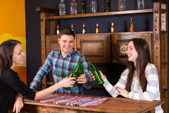 Een bedrijf van jongeren die flessen bier clinking terwijl vervanger royalty-vrije stock afbeeldingen